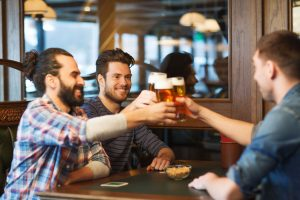 happy male friends drinking beer at pub